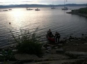 Group launching a canoe on Lake Champlain.